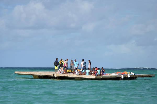 Chiếc bè gỗ rộng khoảng 100 m2 nằm giữa biển cách bờ chừng 2 km là địa điểm chơi môn dù lượn.